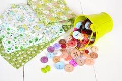 Κομμάτια υφάσματος με το σχέδιο λουλουδιών, πολύχρωμο prong-σύνολο ανασκόπησης κουμπιών κινηματογραφήσεων σε πρώτο πλάνο ράβοντας Στοκ εικόνες με δικαίωμα ελεύθερης χρήσης