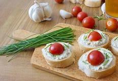 Κομμάτια ψωμιού το λαχανικό που διαδίδονται με, τα φρέσκα κρεμμύδια και τις ντομάτες Στοκ εικόνες με δικαίωμα ελεύθερης χρήσης