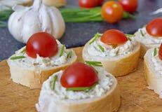Κομμάτια ψωμιού το λαχανικό που διαδίδονται με, το φρέσκο κρεμμύδι και τις ντομάτες Στοκ Φωτογραφίες