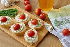 Κομμάτια ψωμιού το λαχανικό που διαδίδονται με, το φρέσκο κρεμμύδι και τις ντομάτες Στοκ Εικόνες