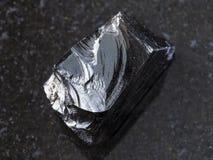 κομμάτι ακατέργαστο Obsidian (ηφαιστειακό γυαλί) στο σκοτάδι Στοκ Εικόνες