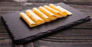 Κομμάτι και φέτες του τυριού σε ένα ξύλινο υπόβαθρο στοκ φωτογραφία με δικαίωμα ελεύθερης χρήσης