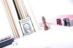 Κομμάτι σκακιού βασιλιάδων εκτός από ένα δολάριο Μπιλ που τυλίγεται σε ένα βιβλίο Στοκ Φωτογραφία
