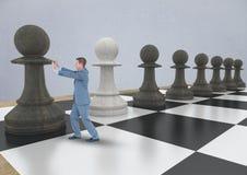 Κομμάτι σκακιού ώθησης επιχειρησιακών ατόμων ενάντια στον γκρίζο τοίχο Στοκ Εικόνα