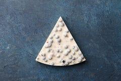 Κομμάτι της άσπρης σοκολάτας με τα μούρα στο μπλε υπόβαθρο στοκ εικόνα με δικαίωμα ελεύθερης χρήσης