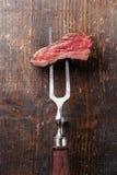 Κομμάτι της μπριζόλας βόειου κρέατος στο δίκρανο κρέατος Στοκ φωτογραφία με δικαίωμα ελεύθερης χρήσης