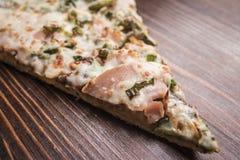Κομμάτι της πίτσας με το ζαμπόν σε ένα καφετί ξύλινο υπόβαθρο Στοκ Εικόνες