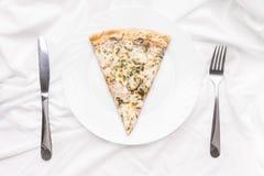 Κομμάτι της πίτσας σε ένα πιάτο, ένα δίκρανο και ένα μαχαίρι σε ένα άσπρο τραπεζομάντιλο Στοκ Φωτογραφίες