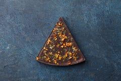 Κομμάτι της σκοτεινής σοκολάτας με το κάλυμμα πάπρικας στο μπλε υπόβαθρο στοκ εικόνες
