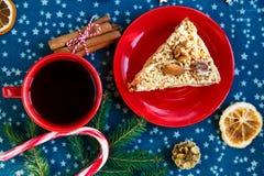 Κομμάτι της χειροποίητης πίτας βερίκοκων στο κόκκινο πιάτο και το κόκκινο φλυτζάνι με το τσάι ή του καφέ με το δέντρο έλατου, πεύ στοκ φωτογραφία με δικαίωμα ελεύθερης χρήσης
