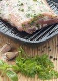Κομμάτι του ακατέργαστου κρέατος που μαρινάρεται με τα χορτάρια, το σκόρδο και το φυτικό έλαιο Στοκ φωτογραφία με δικαίωμα ελεύθερης χρήσης