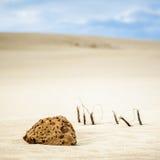Κομμάτι του βράχου στους αμμόλοφους άμμου Στοκ φωτογραφία με δικαίωμα ελεύθερης χρήσης