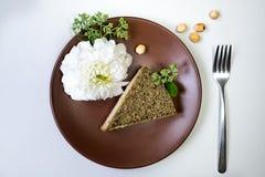 Κομμάτι του κέικ με στο άσπρο υπόβαθρο λουλούδια φρέσκα Στοκ Φωτογραφία