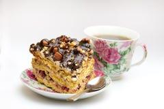 Κομμάτι του κέικ με τα φουντούκια, το κουταλάκι του γλυκού και το φλυτζάνι Στοκ Εικόνα