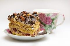 Κομμάτι του κέικ με τα φουντούκια, το κουταλάκι του γλυκού και το φλυτζάνι Στοκ Εικόνες