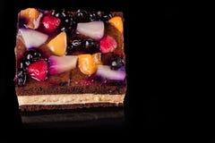 Κομμάτι του κέικ φρούτων με τη ζελατίνα και την κρέμα Μαύρη ανασκόπηση Τοπ όψη Στοκ Φωτογραφίες