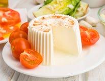 Κομμάτι του μαλακού τυριού με τις ντομάτες κερασιών σε ξύλινο Στοκ Εικόνα