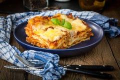 Κομμάτι του νόστιμου καυτού lasagna με το κόκκινο κρασί στοκ εικόνα με δικαίωμα ελεύθερης χρήσης