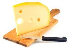 Κομμάτι του ολλανδικού τυριού στον τεμαχίζοντας πίνακα στοκ φωτογραφίες