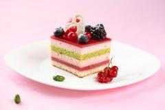 Κομμάτι του πολυστρωματικού Mousse μούρων και φυστικιών κέικ στοκ φωτογραφίες με δικαίωμα ελεύθερης χρήσης