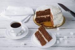 Κομμάτι του σπιτικών κέικ και του καφέ σε έναν άσπρο ξύλινο πίνακα Biscu Στοκ Εικόνες