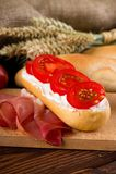 Κομμάτι του baguette με το φρέσκες gervais τυρί και τις ντομάτες κρέμας Στοκ φωτογραφία με δικαίωμα ελεύθερης χρήσης