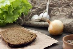 Κομμάτι το μαύρα ψωμί, το μαρούλι, και το chesnou κρεμμυδιών Στοκ φωτογραφία με δικαίωμα ελεύθερης χρήσης