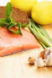 Κομμάτι των ακατέργαστων ψαριών σολομών με το ψωμί και τα λαχανικά Στοκ Εικόνες