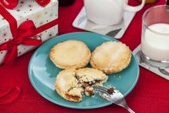 Κομματιάστε τις πίτες και ένα ποτήρι του γάλακτος σε έναν κόκκινο πίνακα Χριστουγέννων Στοκ Εικόνες