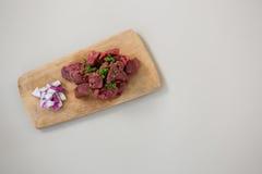 Κομματιασμένο βόειο κρέας και τεμαχισμένα κρεμμύδια στον ξύλινο δίσκο Στοκ Φωτογραφία