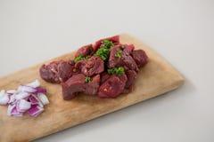 Κομματιασμένο βόειο κρέας και τεμαχισμένα κρεμμύδια στον ξύλινο δίσκο Στοκ Φωτογραφίες