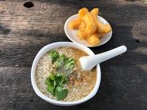 Κομματιασμένο congee χοιρινού κρέατος με το τσιγαρισμένο σκόρδο και λαχανικό στο άσπρο κύπελλο Εξυπηρετήστε με το τσιγαρισμένο ρα στοκ εικόνα με δικαίωμα ελεύθερης χρήσης