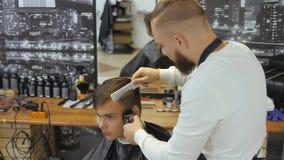 Κομμωτής για τα άτομα barbra Ένας νέος τύπος παίρνει ένα κούρεμα και μια υπηρεσία προσοχής τρίχας από ένα γενειοφόρο άτομο με μια απόθεμα βίντεο