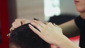 Κομμωτής γυναικών που κάνει το κούρεμα στο νεαρό άνδρα Αυτή που χρησιμοποιεί το ψαλίδι και τη χτένα φιλμ μικρού μήκους