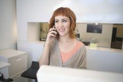 Κομμωτής που απαντά στο κινητό τηλέφωνο στην υποδοχή στο σαλόνι Στοκ εικόνα με δικαίωμα ελεύθερης χρήσης