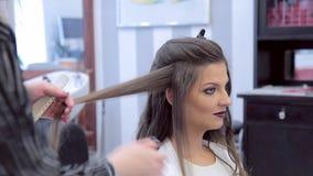 Κομμωτής που εφαρμόζει τη λακ, μια χτένα και τα ρόλερ τρίχας του προτύπου hairstyle απόθεμα βίντεο