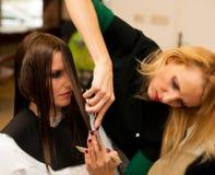 Κομμωτής που κάνει την επεξεργασία τρίχας σε έναν πελάτη στο σαλόνι Στοκ Φωτογραφία