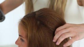 Κομμωτής που κάνει τον όγκο hairstyle και που καθορίζει με τον ψεκασμό τρίχας στο σαλόνι ομορφιάς κοντά επάνω Hairstylist που κάν απόθεμα βίντεο