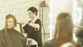 Κομμωτής που κάνει hairstyle με τις λαβίδες και τη χτένα τρίχας για την τρίχα που ισιώνει στο σαλόνι ομορφιάς Στενός κομμωτής upf απόθεμα βίντεο