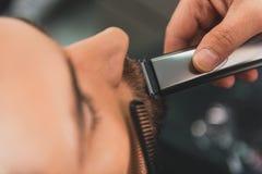 Κομμωτής που ξυρίζει το ανθρώπινο moustache από τον κουρευτή ζώων Στοκ εικόνα με δικαίωμα ελεύθερης χρήσης