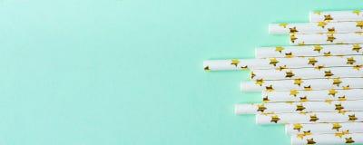 Κομψά άχυρα κατανάλωσης της Λευκής Βίβλου με το χρυσό σχέδιο αστεριών που διασκορπίζεται στο τυρκουάζ υπόβαθρο Χαμηλή γωνία Διασκ Στοκ εικόνες με δικαίωμα ελεύθερης χρήσης