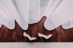 Κομψά νυφικά παπούτσια που βρίσκονται στο ξύλινο πάτωμα δίπλα στο παράθυρο Στοκ εικόνες με δικαίωμα ελεύθερης χρήσης