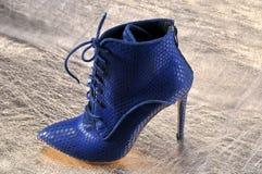 Κομψά παπούτσια γυναικών ` s σε ένα κομμάτι του υλικού από το χρυσό δέρμα Στοκ Εικόνες