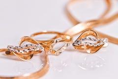 Κομψά χρυσά σκουλαρίκια και ένα δαχτυλίδι από το ίδιο σύνολο Στοκ φωτογραφία με δικαίωμα ελεύθερης χρήσης