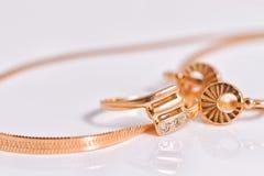 Κομψά χρυσά σκουλαρίκια και ένα δαχτυλίδι από το ίδιο σύνολο Στοκ Φωτογραφίες
