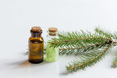 Κομψά aromatherapy ουσιαστικά έλαια και άλας βελόνων στα μπουκάλια στο άσπρο επιτραπέζιο υπόβαθρο Στοκ Φωτογραφίες