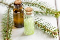 Κομψά aromatherapy ουσιαστικά έλαια και άλας βελόνων στα μπουκάλια στο άσπρο επιτραπέζιο υπόβαθρο Στοκ Εικόνες