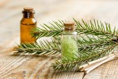 Κομψά aromatherapy ουσιαστικά έλαια και άλας βελόνων στα μπουκάλια στο ξύλινο επιτραπέζιο υπόβαθρο Στοκ φωτογραφία με δικαίωμα ελεύθερης χρήσης
