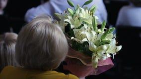 Κομψή ανώτερη συναυλία γυναικείας προσοχής, που κρατά τη δέσμη των όμορφων λουλουδιών lilium απόθεμα βίντεο