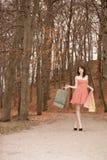 Κομψή γυναίκα αγοραστών που περπατά στο πάρκο μετά από να ψωνίσει Στοκ Φωτογραφίες